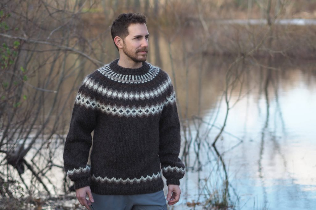 man wearing Turf and Clouds Lopi sweater outside near pond