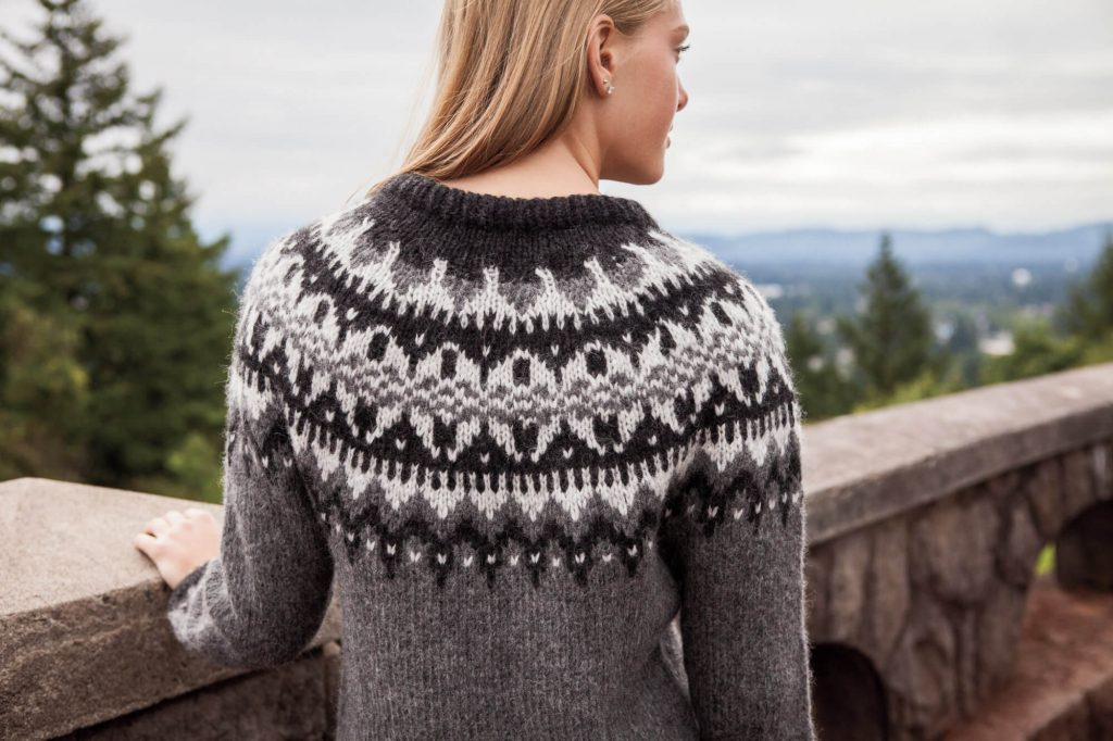 Woman wearing Eldfell Pullover in grey tones, from back