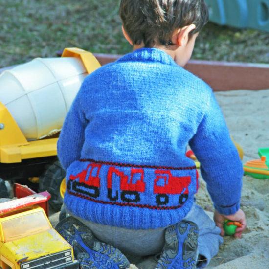 boy wearing Construction Trucks Sweater while in sandbox