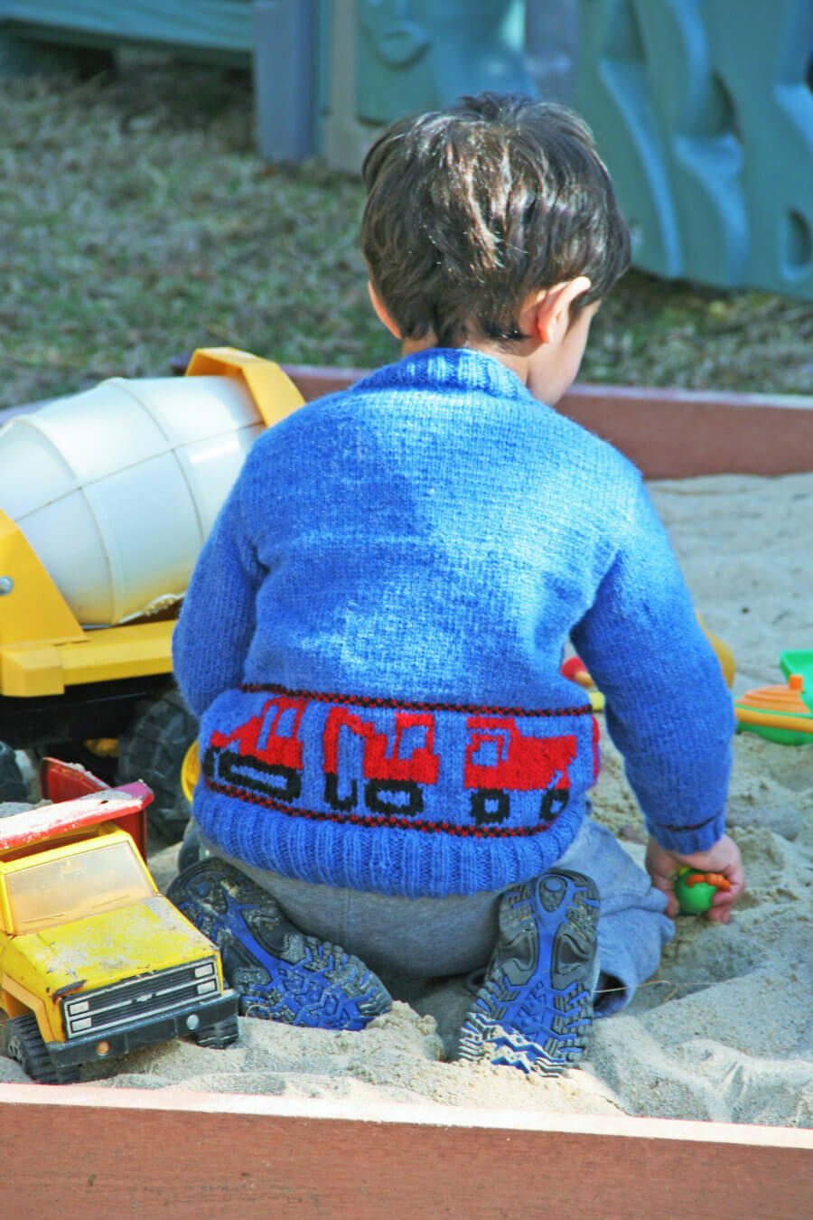 boy wearing Construction Trucks Sweater while in sandbox