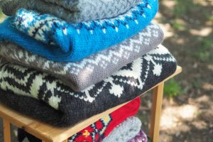 Stack of hand knit sweaters on a table